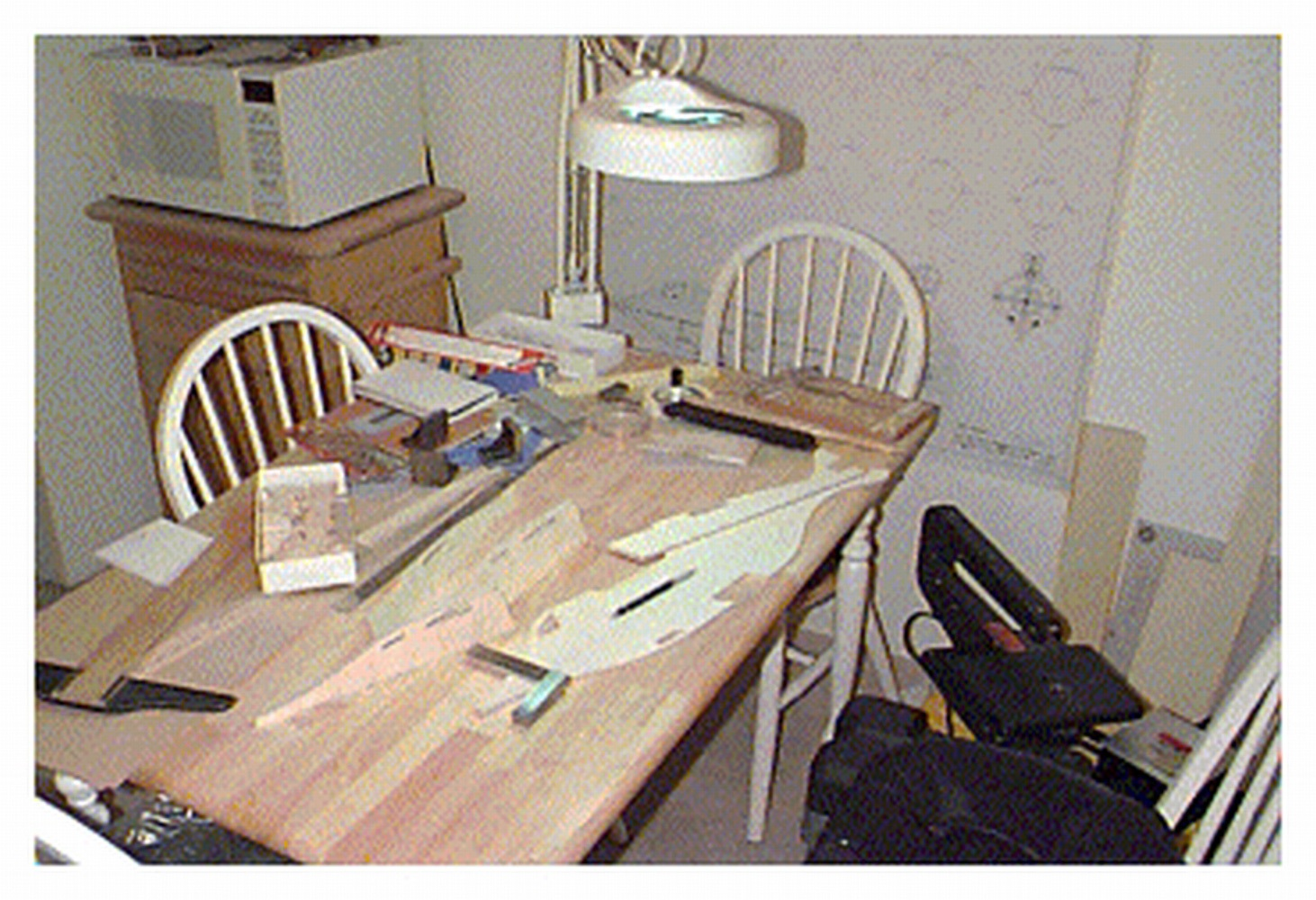 My kitchen table workshop with my CAD/CAM drawing on the wall and table top and the plywood keel pieces. Bass wood bulkheads are in the box